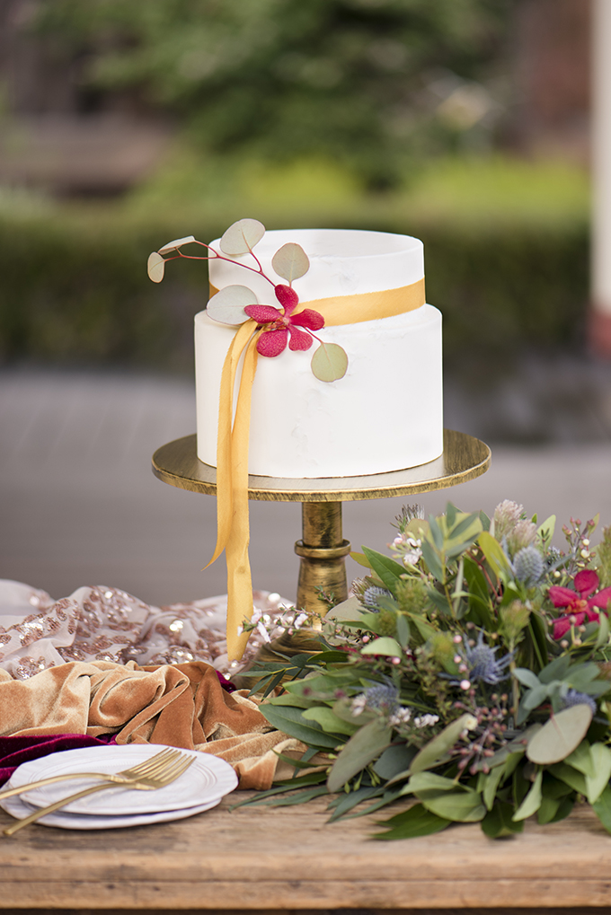 The wedding cake was a simple white one, with a mustard ribbon, greenery and a bloom