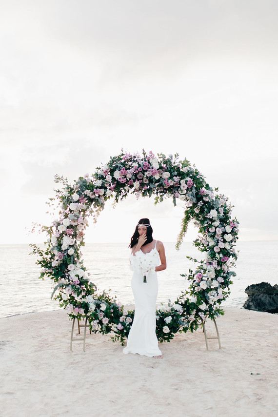 The wedding ceremony arch was a circle of blush, white blooms and fresh greenery