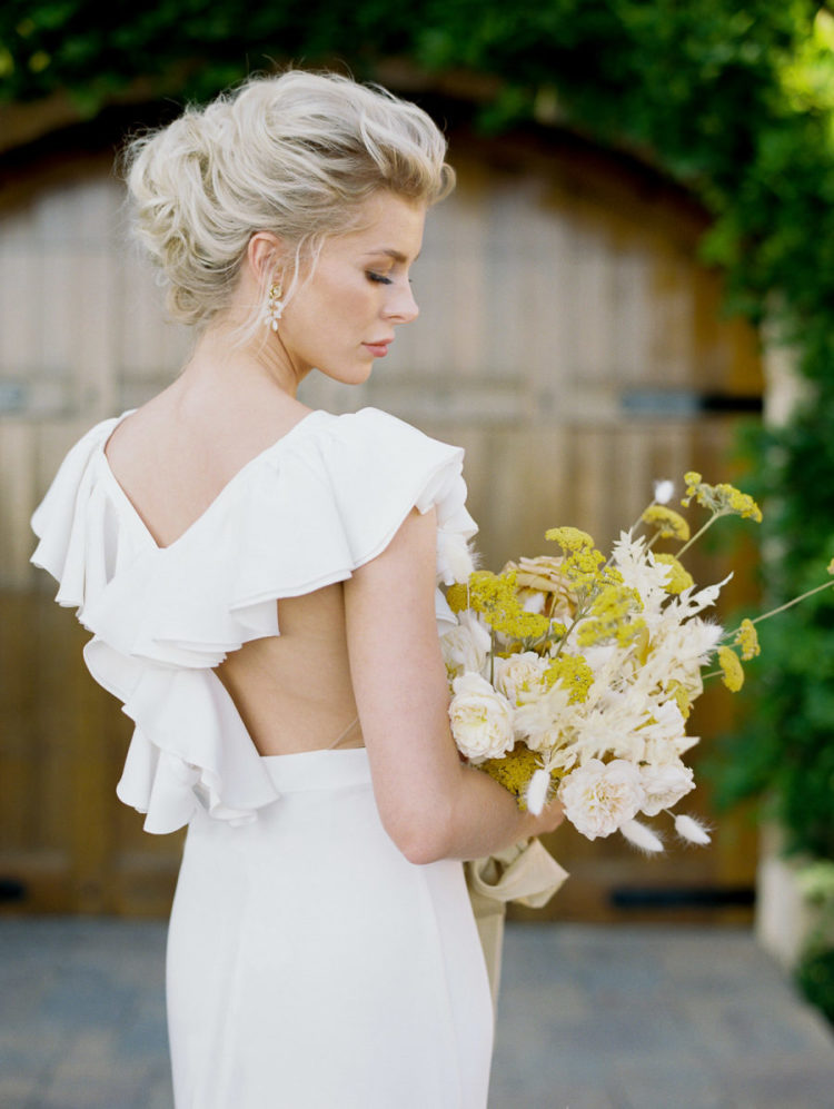 The wedding dress featured a ruffled racerback, the bride was carrying a chic bouquet with yellow and creamy blooms and grasses