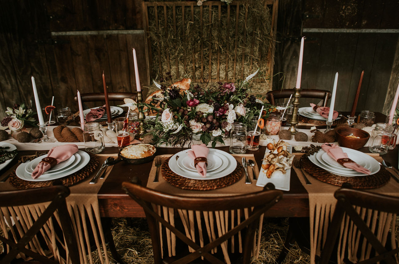 The wedding tablescape was done with pink napkins, wicker chargers, fringe placemat, various candles and a lush floral centerpiece