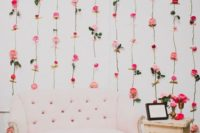 08 a refined wedding photo booth backdrop of fresh blooms attached with masking tape and a pink couch
