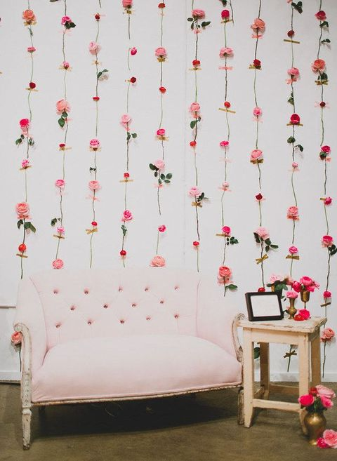 a refined wedding photo booth backdrop of fresh blooms attached with masking tape and a pink couch