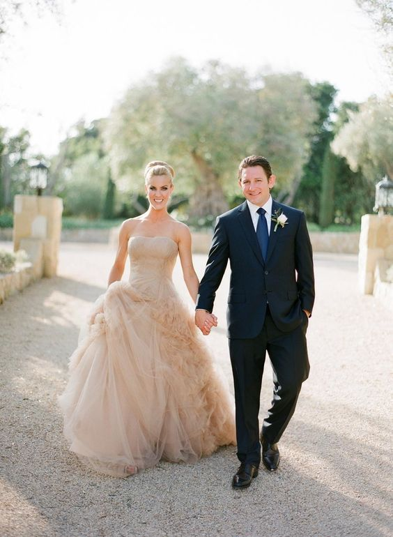 a strapless wedding ballgown with a whimsically draped skirt done in tan color looks unusual