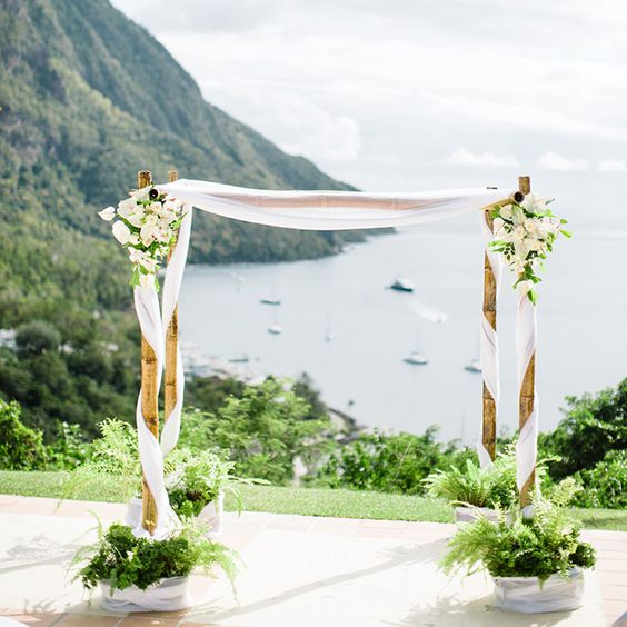 a bamboo wedding arch interwoven with white flowy fabric, lush neutral blooms and greenery plus greenery at the base
