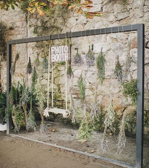 a frame with herbs and greenery hanging down and a swing is a fun and unusual idea