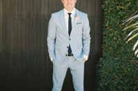 09 a light blue suit, a white shirt and a black tie plus neutral sneakers and a blush boutonniere is a cool spring outfit