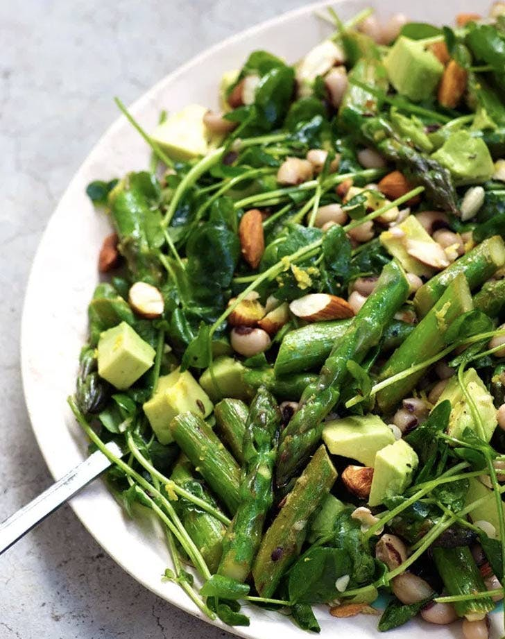 a salad of asparagus, avocado,greenery, beans and almonds is a delicious and fresh idea