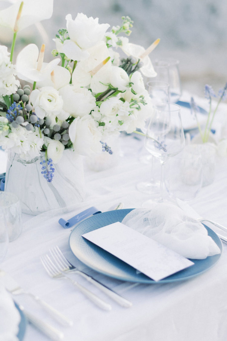 The wedding table was done in white and blues with a lush floral centerpiece, blue chargers and neutrals