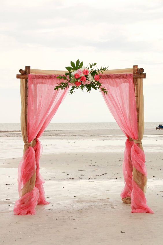 a cute pink wedding arch for a beach wedding