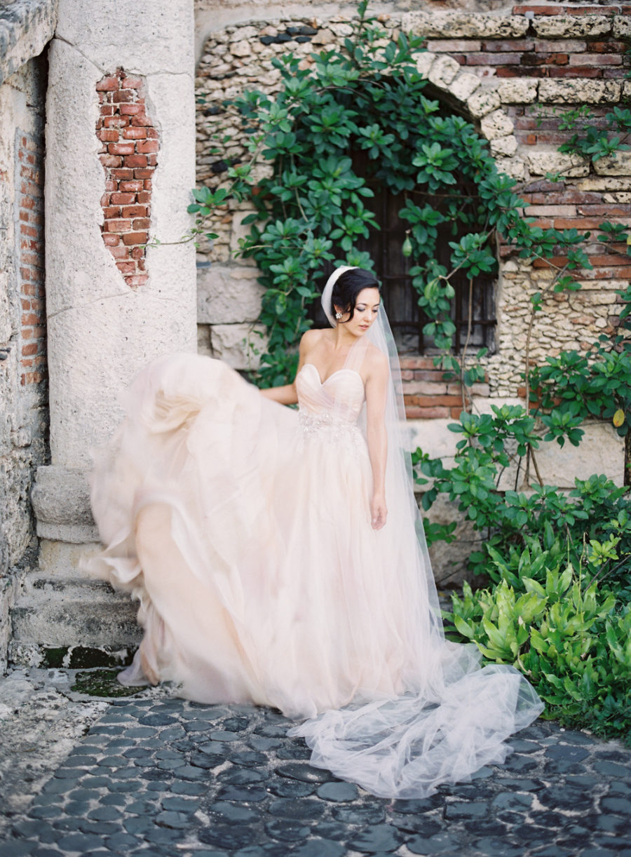 a blush strapless wedding ballgown with a sweetaheart neckline and a layered skirt with a train