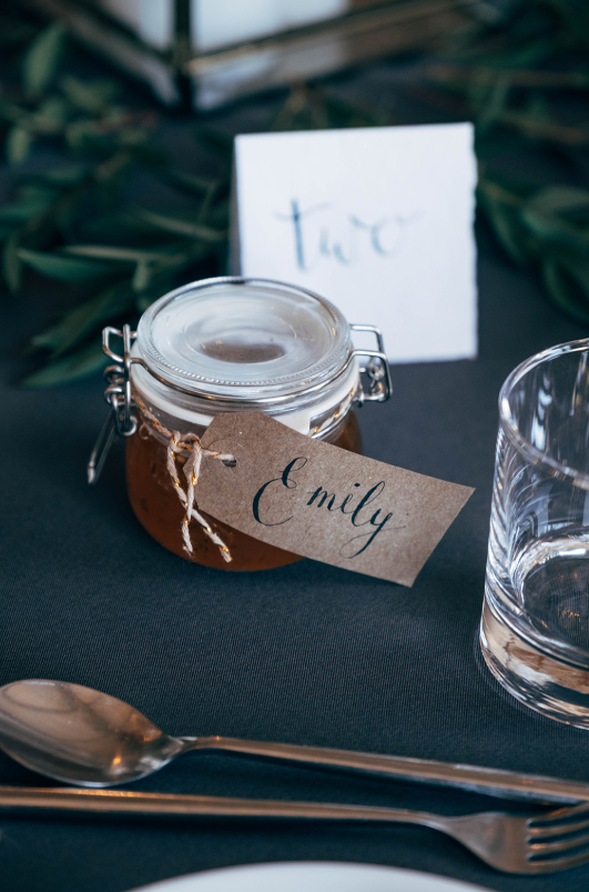 Homemade jam jars were offered as wedding favors and card holders