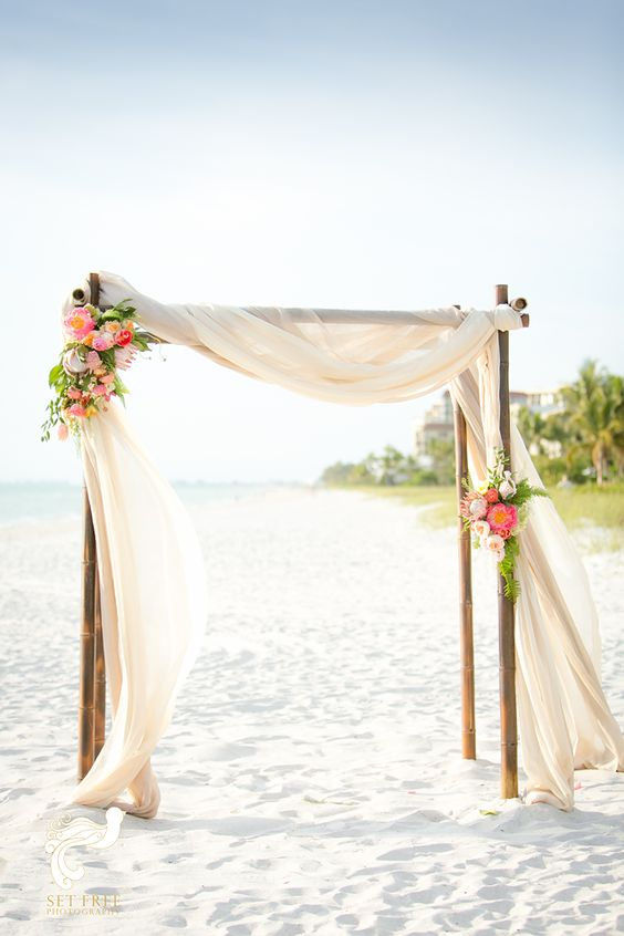 a bamboo wedding arch with neutral flowy amd airy fabric, greenery and pink and white blooms