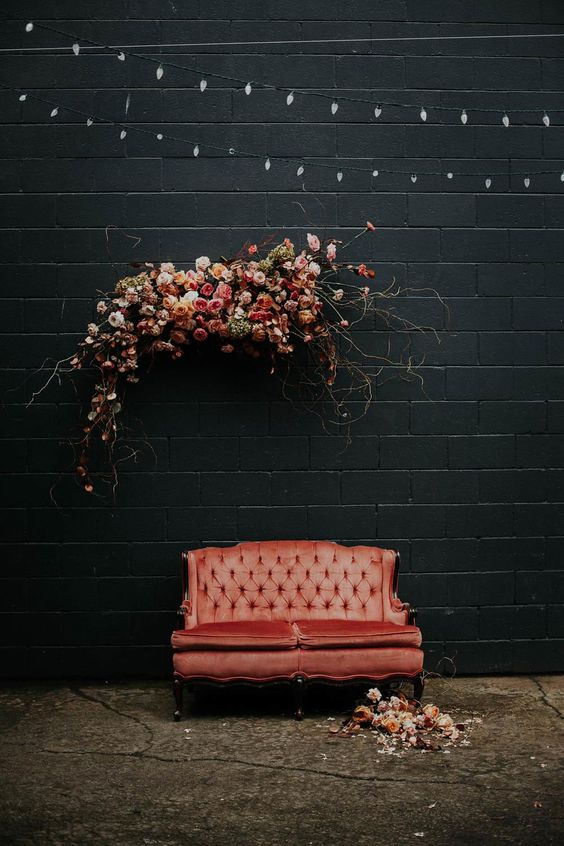 a chic photo booth with a refined coral sofa, a lush floral installation and blooms and petals