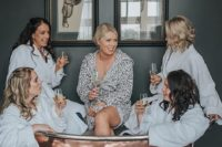 11 the bride and her bridesmaids have fun on the morning of her wedding day in a chic vintage copper bathtub