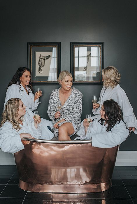 the bride and her bridesmaids have fun on the morning of her wedding day in a chic vintage copper bathtub
