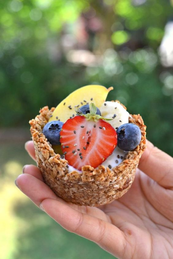 vegan granola cups with cinnamon, nuts, coconut oil and topped with fresh fruits and berries