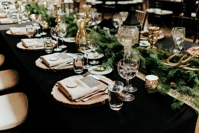 The reception tables were done with fir branches, antlers, wood slice chargers and metallic touches