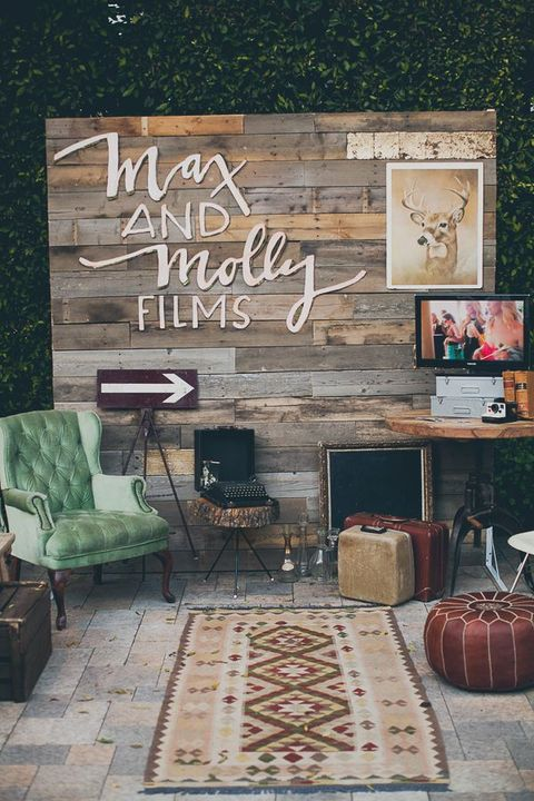 a chic vintage photo booth with a weathered wood wall, refined furniture and signs and artworks