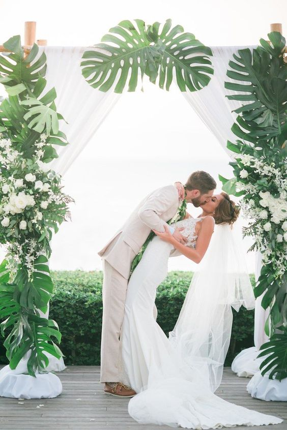 a gorgeous tropical wedding arch decorated with white flowy curtains, monstera leaves and white blooms