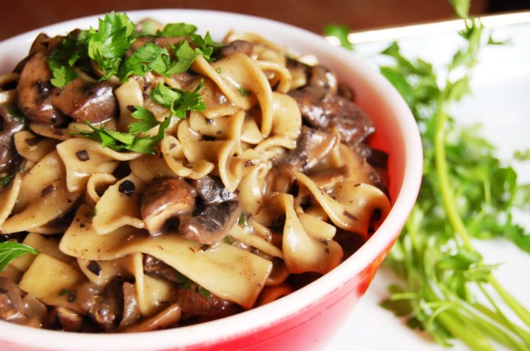 a mushroom stroganoff of ribbon noodles, oilve oil, mushrooms, onions, with a white wine sauce