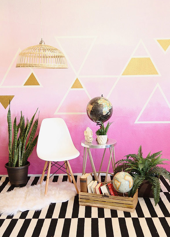 a colorful boho backdrop with triangles, some potted plants, a pendant lamp, a chair and globes