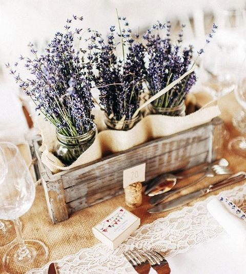 a cozy Provence-inspired wedding centerpiece of a wooden crate and lavender in jars