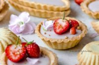 13 vegan and refined sugar-free coconut panna cotta tartlets topped with strawberrries and flower petals