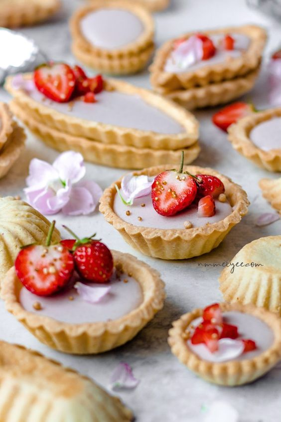 vegan and refined sugar-free coconut panna cotta tartlets topped with strawberrries and flower petals