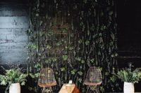 14 a cool boho wedding booth backdrop – a dark wall with greenery, a couple of cool chairs and a geometric table