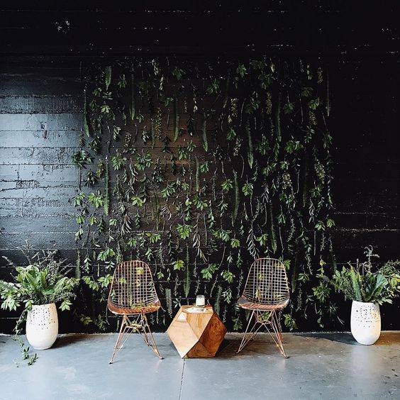 a cool boho wedding booth backdrop - a dark wall with greenery, a couple of cool chairs and a geometric table