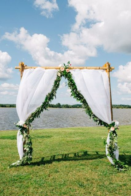 a bamboo wedding arch with white curtains, greenery and blush blooms on the lake shore
