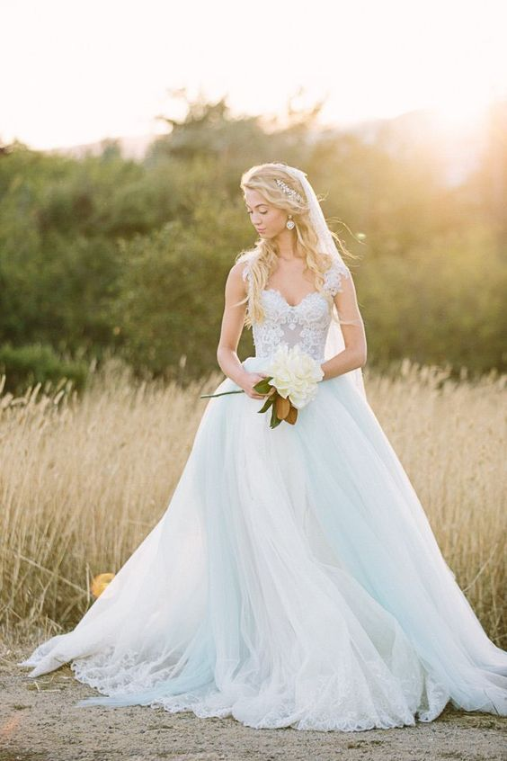 a light blue princess style wedidng ballgown with a lace bodice and thick straps and a layered skirt