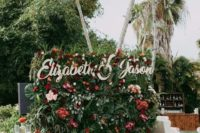 15 a lush tropical photo booth backdrop of much greenery and foliage and bright blooms plus names