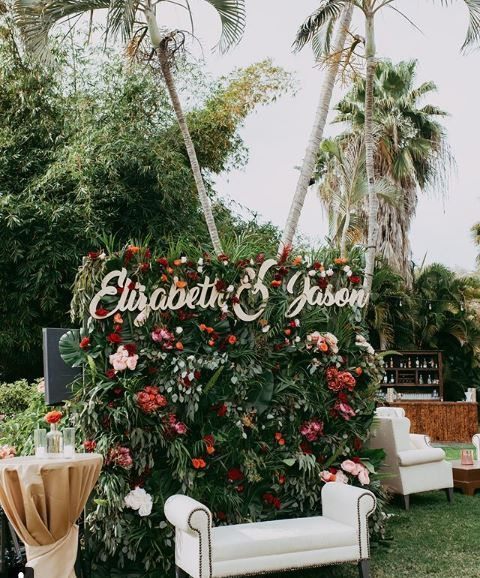 a lush tropical photo booth backdrop of much greenery and foliage and bright blooms plus names