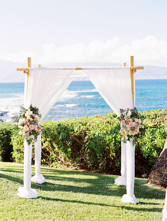 a bamboo wedding arch with white flowy and airy curtains, pink and white flowers and greenery
