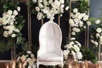 16 a luxurious wedding photo booth with much greenery and white blooms, candles and a refined statement chair