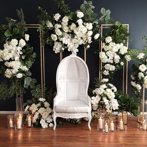 a luxurious wedding photo booth with much greenery and white blooms, candles and a refined statement chair