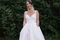 16 a minimalist wedding ballgown with spaghetti straps, a pleated skirt with a train and pockets