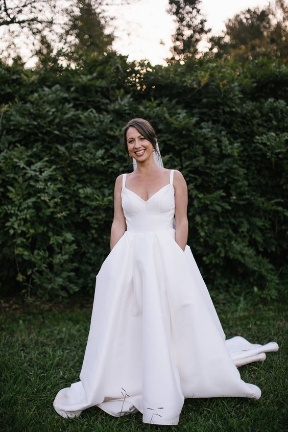 a minimalist wedding ballgown with spaghetti straps, a pleated skirt with a train and pockets
