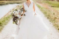 17 a modern wedding ballgown with a plunging neckline with a plain bodice, no sleeves and a full layered skirt