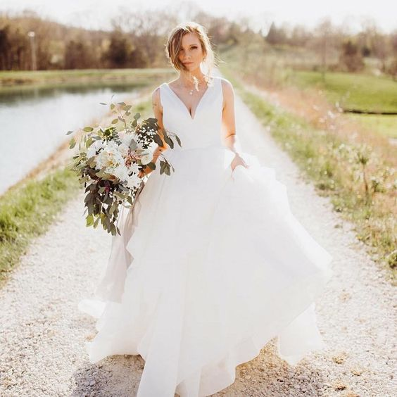 a modern wedding ballgown with a plunging neckline with a plain bodice, no sleeves and a full layered skirt