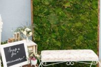 17 a moss wall backdrop with buntings, a refined bench and vintage suitcases for a garden wedding