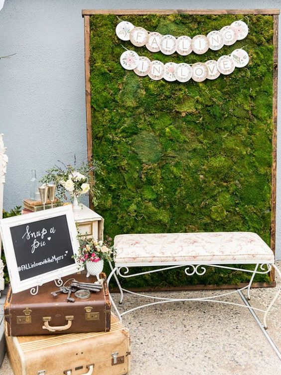a moss wall backdrop with buntings, a refined bench and vintage suitcases for a garden wedding