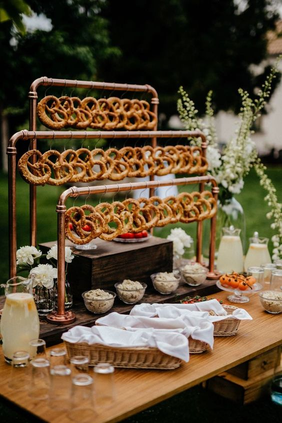 a stylish industrial pretzel bar with copper pipes and pretzels on hooks, with dips and veggies