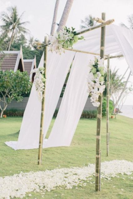 a bamboo wedding arbor decorated with white curtains, white and green blooms and greenery