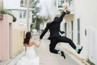 18 a groom jumping up as he's happy to get married is a fun wedding portrait idea to add a playful touch