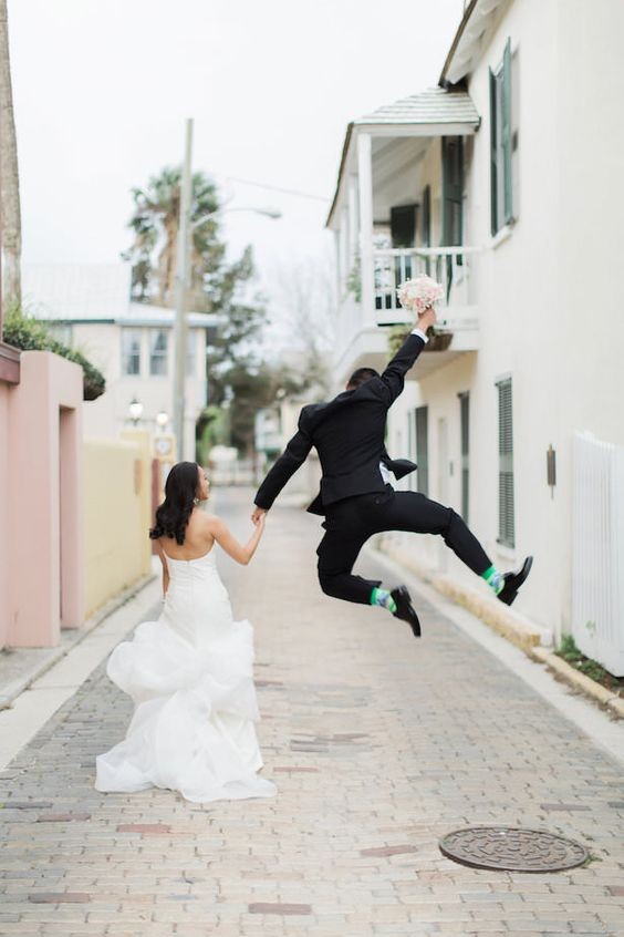 a groom jumping up as he's happy to get married is a fun wedding portrait idea to add a playful touch