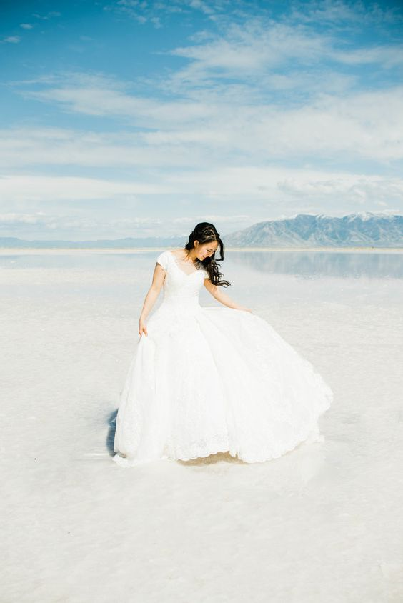 a plain wedding ballgown  with a deep V neckline and a full skirt plus a lace back