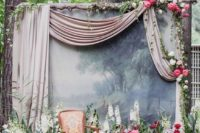 18 a refined wedidng photo booth backdrop with a wall decorated with airy fabric, blod blooms on it and around it and a refined chair