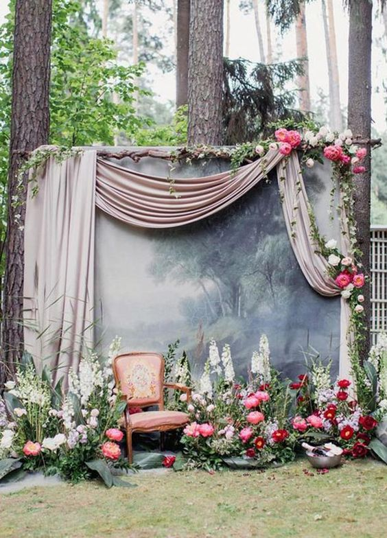 a refined wedidng photo booth backdrop with a wall decorated with airy fabric, blod blooms on it and around it and a refined chair